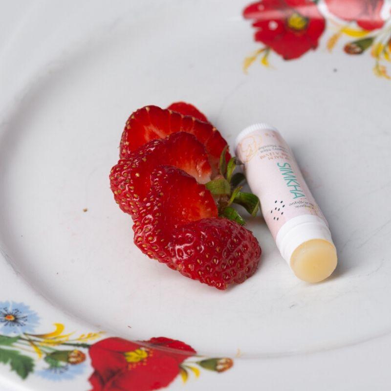 Photo de baume à lèvres fraise menthe sur une assiette de fraises