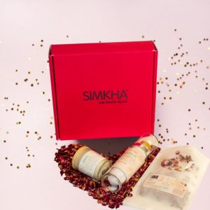 Boite cadeau mixte rose contenant des soins de la peau avec des pétales de roses et une bougie